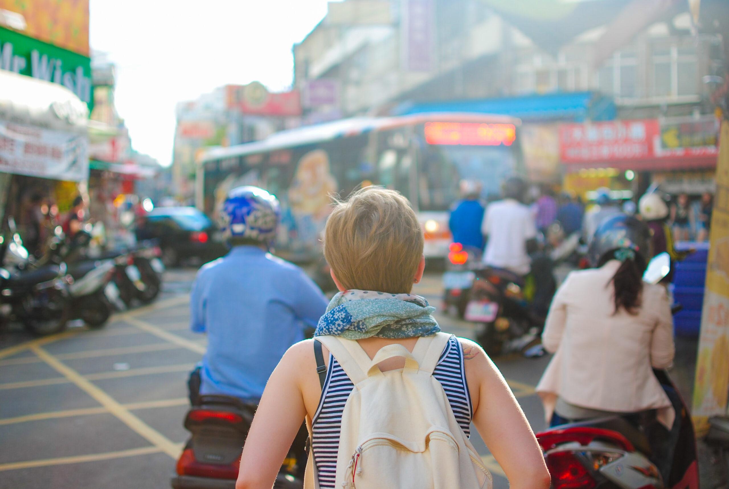 girl walks through crowd of mopeds